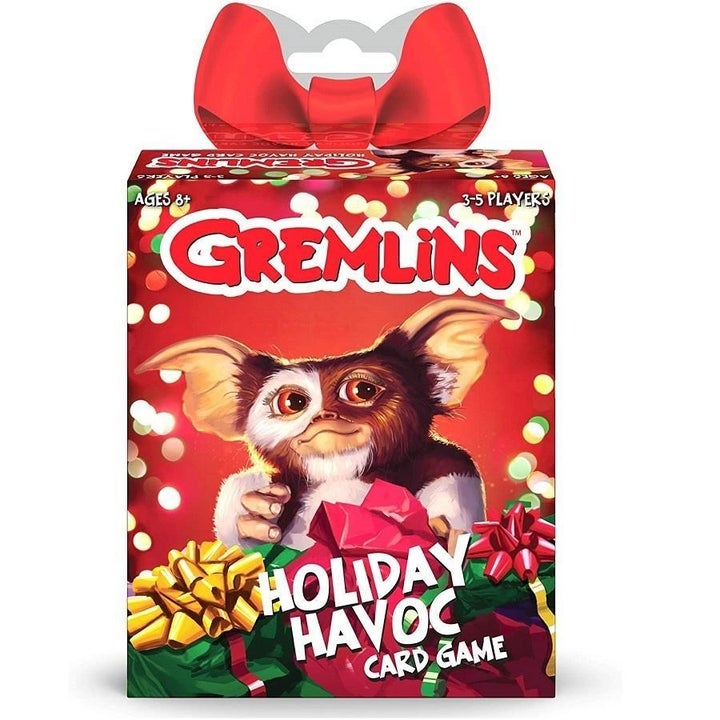 the card box with a red bow on top and a photo of a gremline on the front with Christmas lights