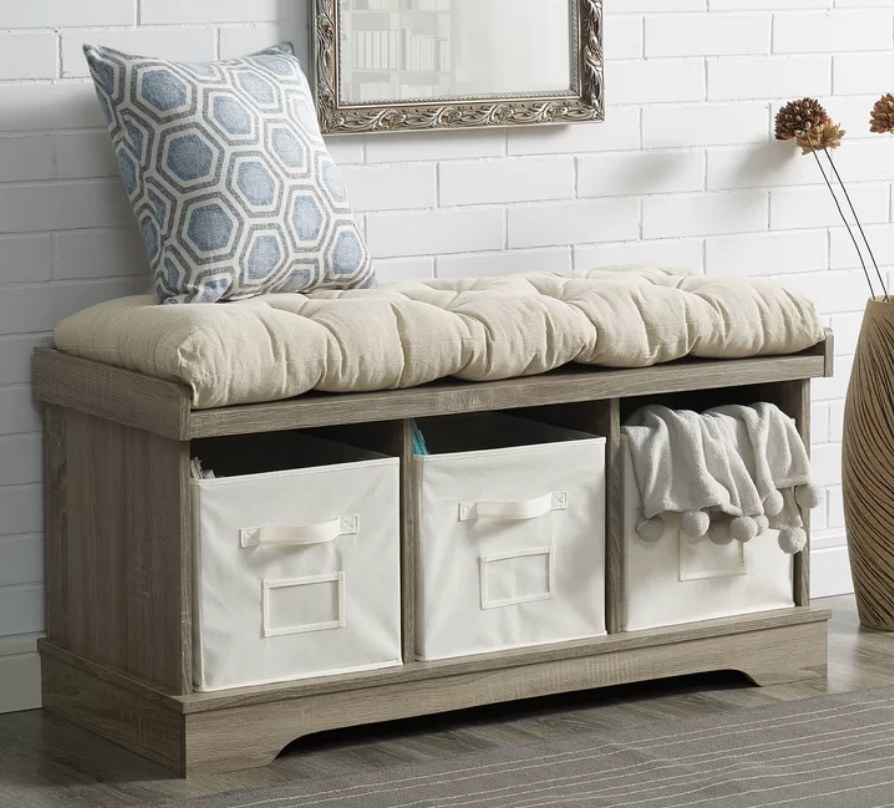 Light wood storage bench with three fabric storage bins and beige cushion on top