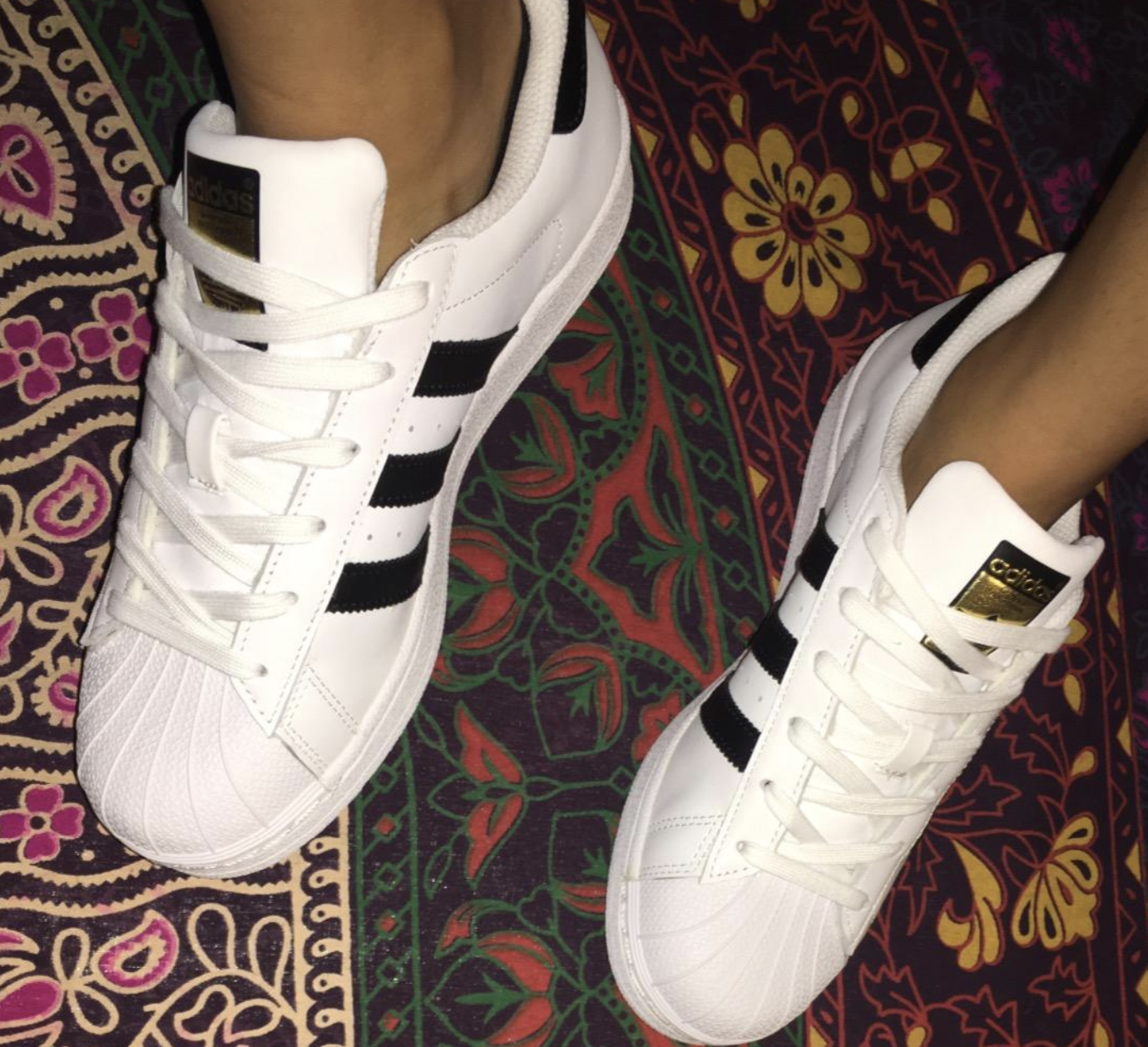 a reviewer wearing the white, black, and gold adidas sneakers