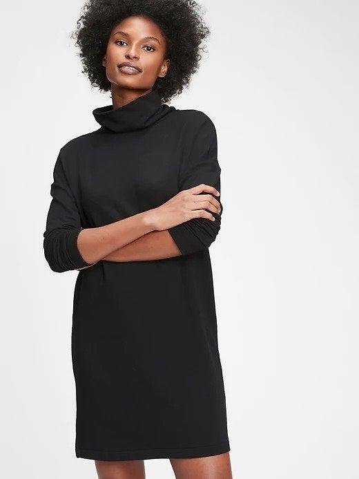 Model wearing black turtleneck sweater dress