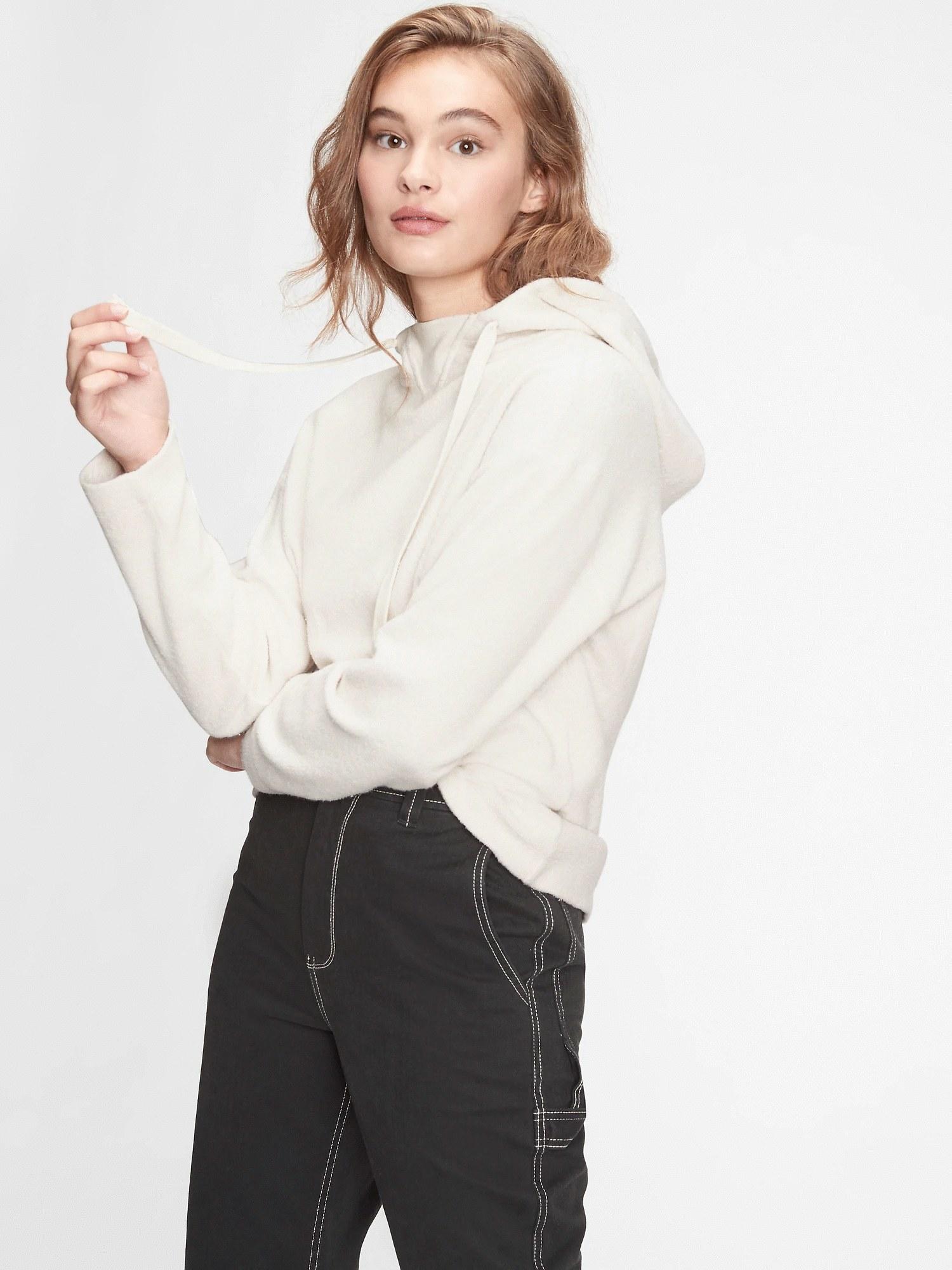 Model wearing cream hoodie