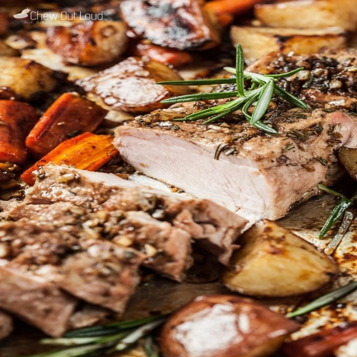 A roasted pork tenderloin with herbs and roasted veggies on the side.
