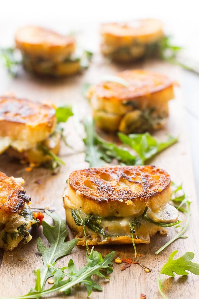 Several mini grilled cheese sandwiches with arugula on a serving board.
