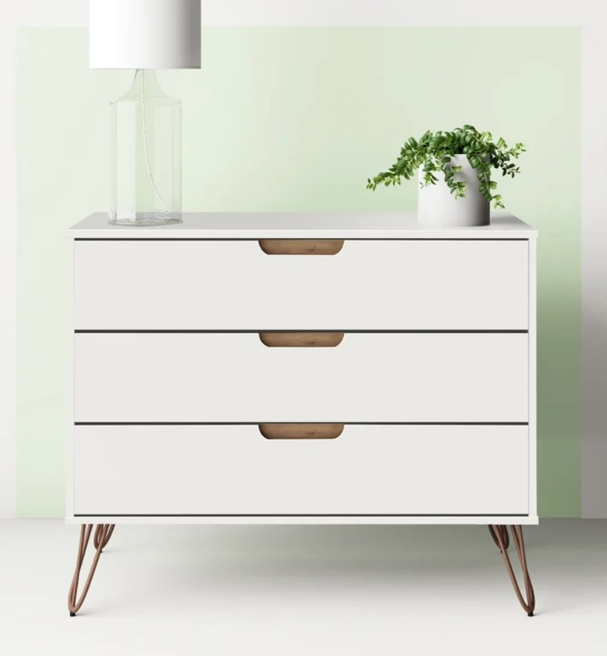 White three drawer dresser with brown legs, lamp and plant on top