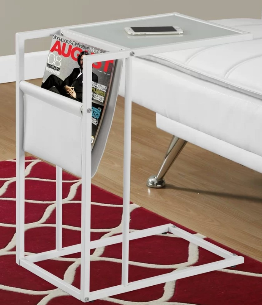 White end table with white magazine pocket and extendable clear table top