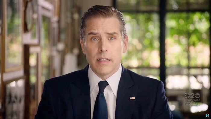 Hunter Biden wears a suit with a US flag pin, addressing the camera