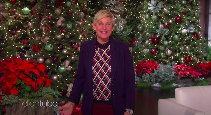 Ellen DeGeneres smiles and wears a festive holiday sweater and jacket on her talk show, standing in front of Christmas trees, decorated with lights and ornaments