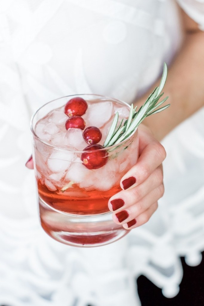 Someone holding a Bourbon cranberry cocktail.