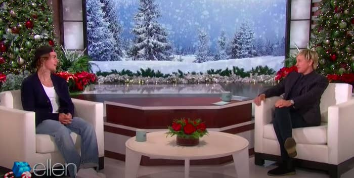 Justin Bieber, wearing jeans and a backward cap, sits in a white chair across from Ellen DeGeneres, wearing dark-colored clothing, on her talk show, which is decorated with Christmas trees and a wintry, snow-filled animation behind them