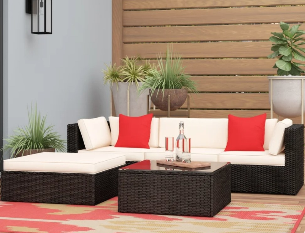 Brown outdoor sofa with beige cushions and red pillows, matching table with glass top