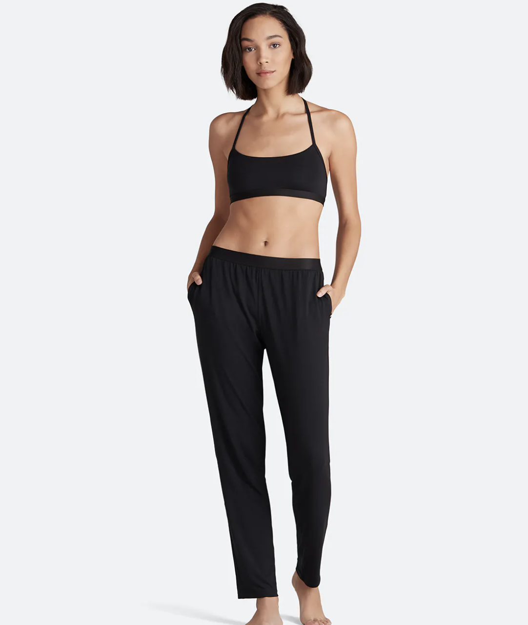 Model wearing the longe pants in black with loose fit and pockets on either side