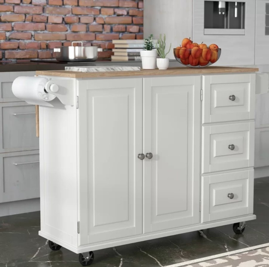 White kitchen car with double cabinets, three drawers, paper towel holder and wooden top
