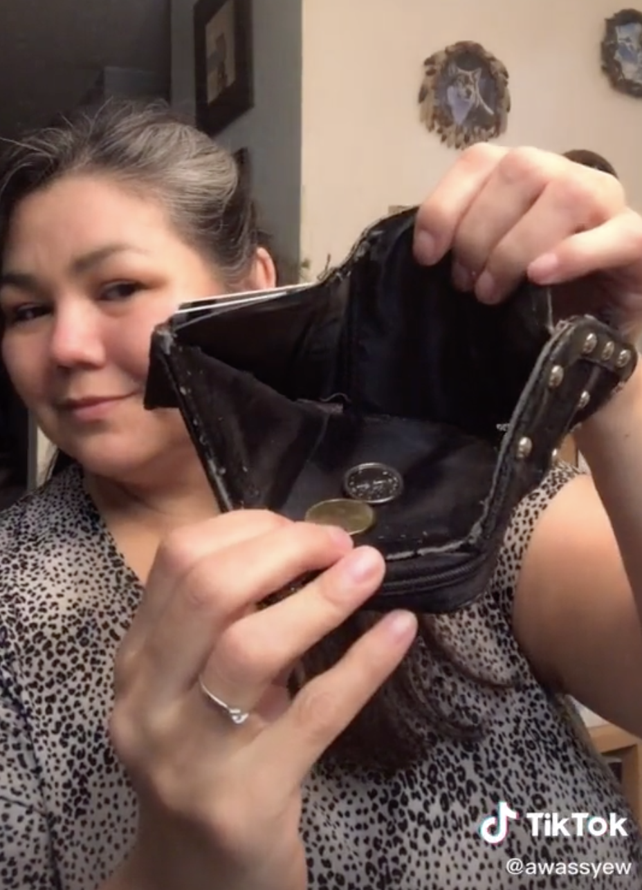Woman holding up a wallet with just a bit of change.