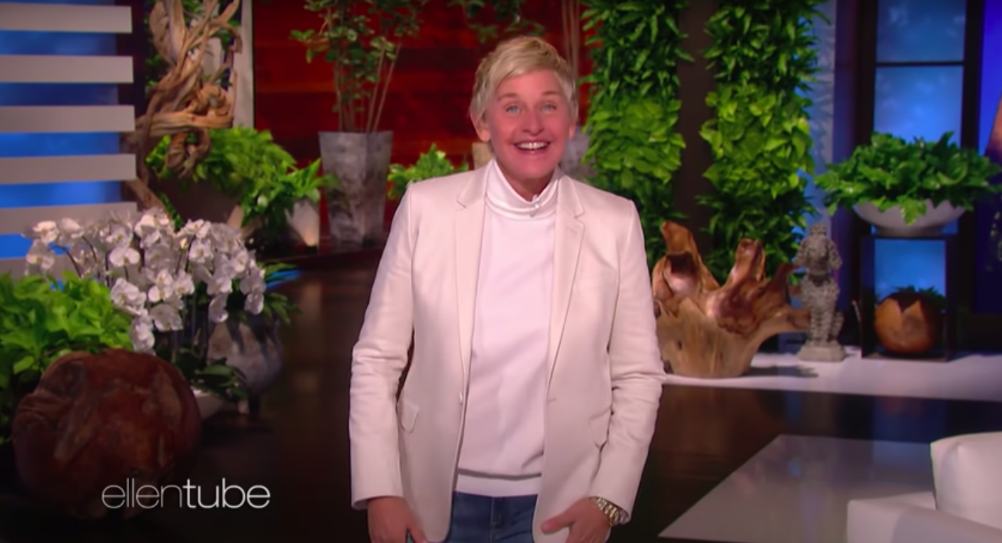 Ellen DeGeneres, wearing a white blazer and turtleneck, smiles widely at the camera