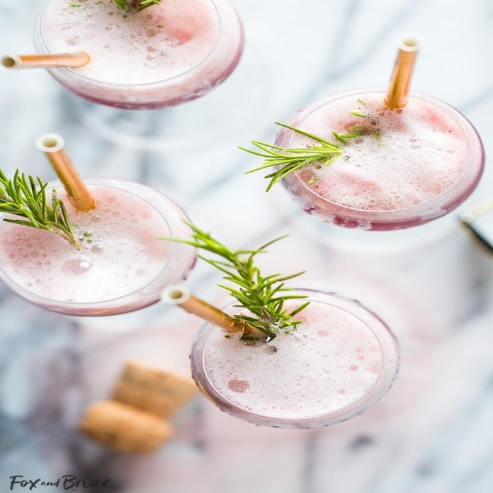 Four champagne glasses filled with sorbet mimosas, topped with sprigs of rosemary.