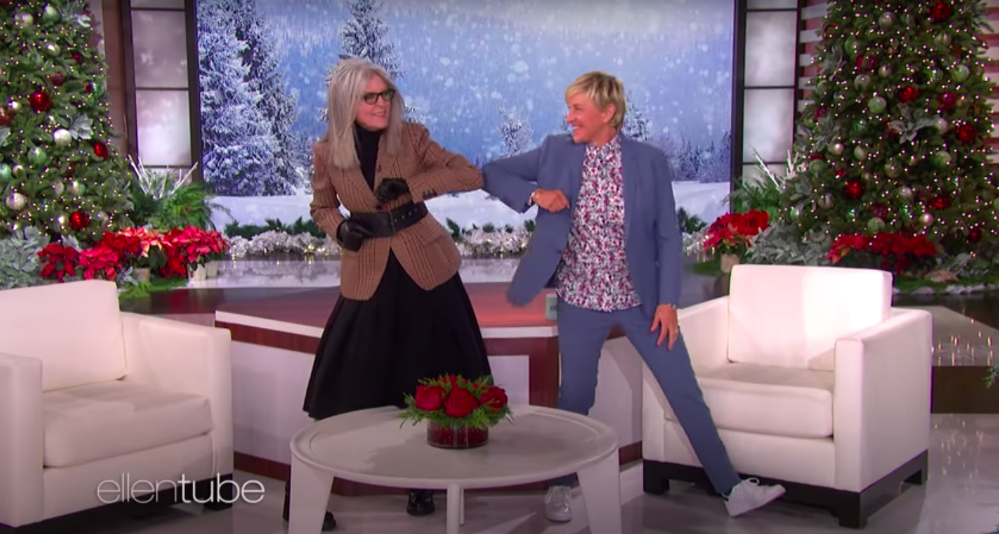 Diane Keaton, wearing a jacket and black gloves, dances with a smiling Ellen DeGeneres, dressed in a blue blazer and floral shirt, as the TV show's set is decorated with Christmas trees