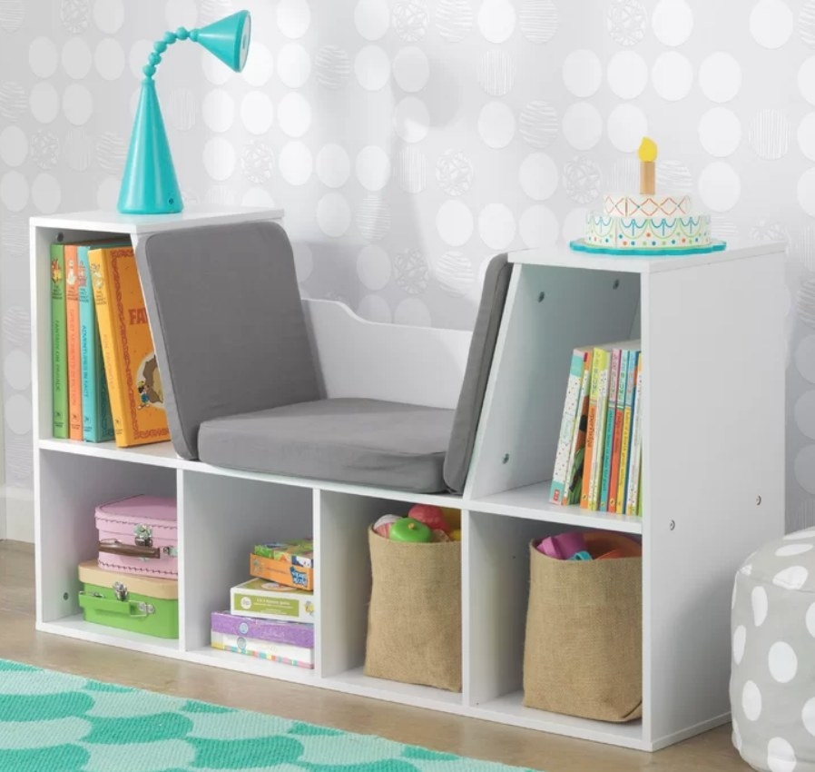 White reading nook with four bottom cubbies, gray cushioned seat in the middle with a shelf on both sides