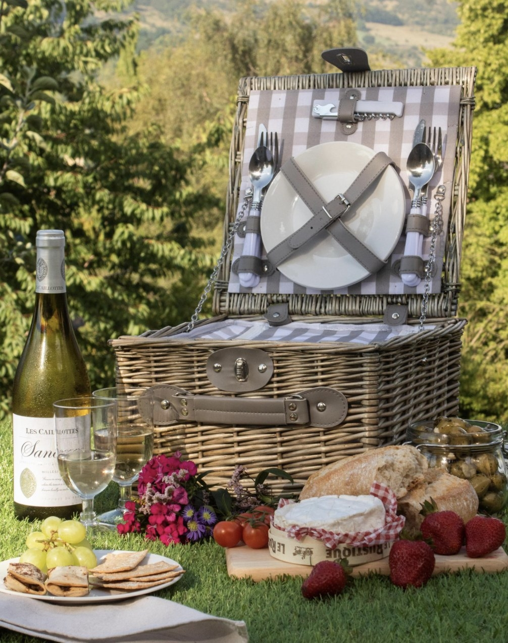 The picnic basket with gingham lining and strapped-in plates, cutlery, and a bottle opener
