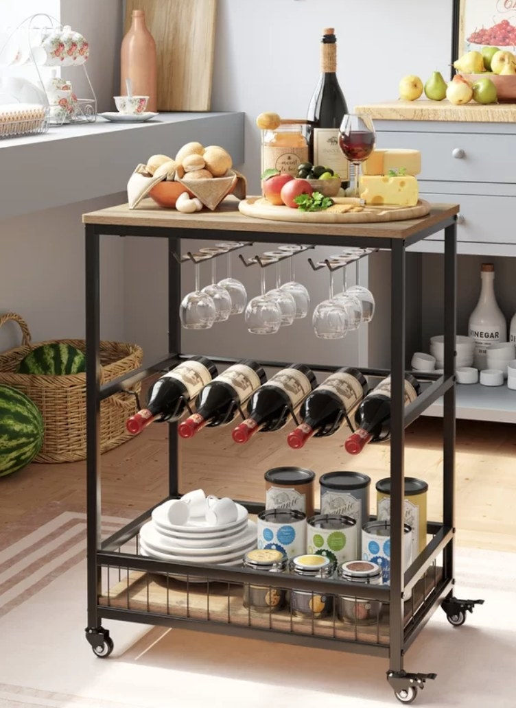 Black framed bar cart with wooden top, storage cubby on the bottom, wine bottle rack in the middle, and wine glass rack underneath table top