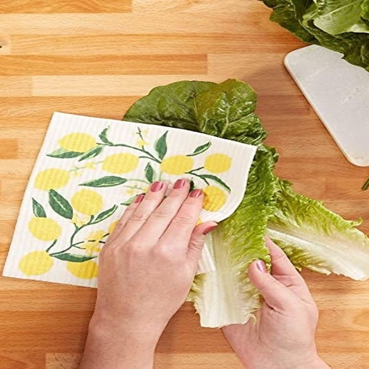 A hand wiping down a head of lettuce with a Swedish Dishcloth printed with lemons