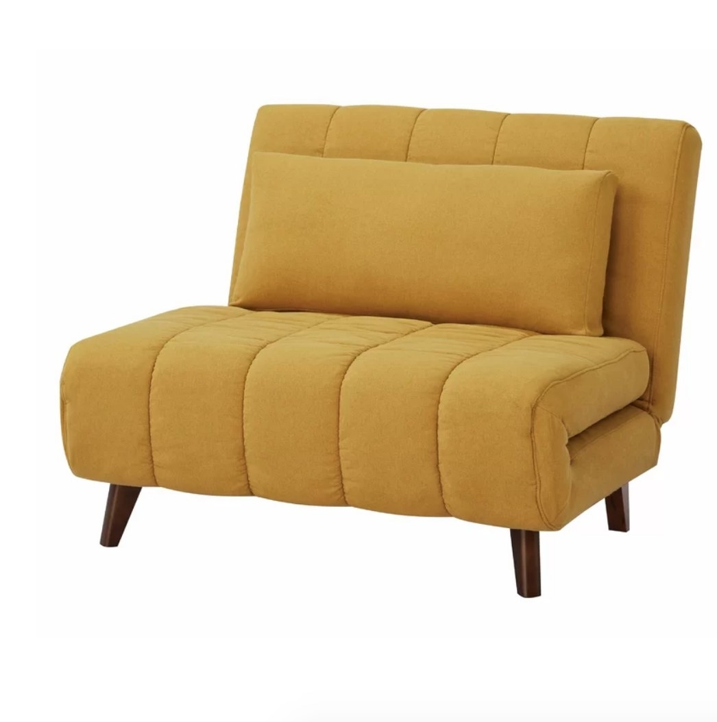Yellow cushioned convertible chair with yellow pillow and brown legs
