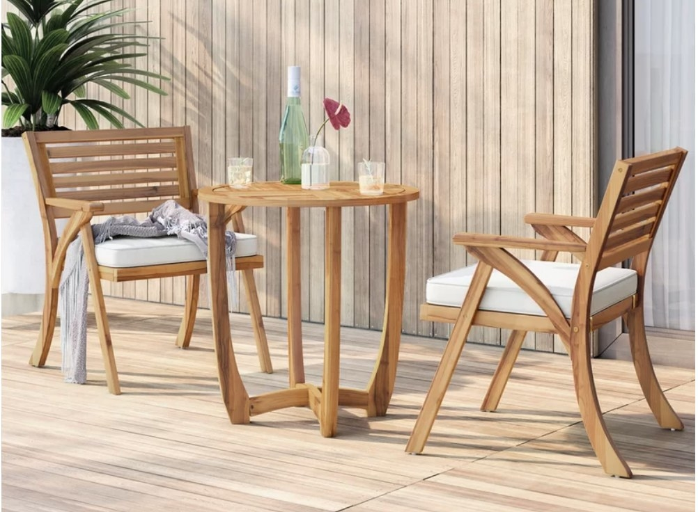 Wooden bistro set with two wooden chairs with white cushions, round wooden table in the middle with bottles and glasses on it
