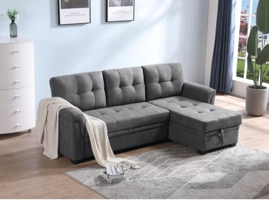 Gray sleeper sectional sofa with off-white throw