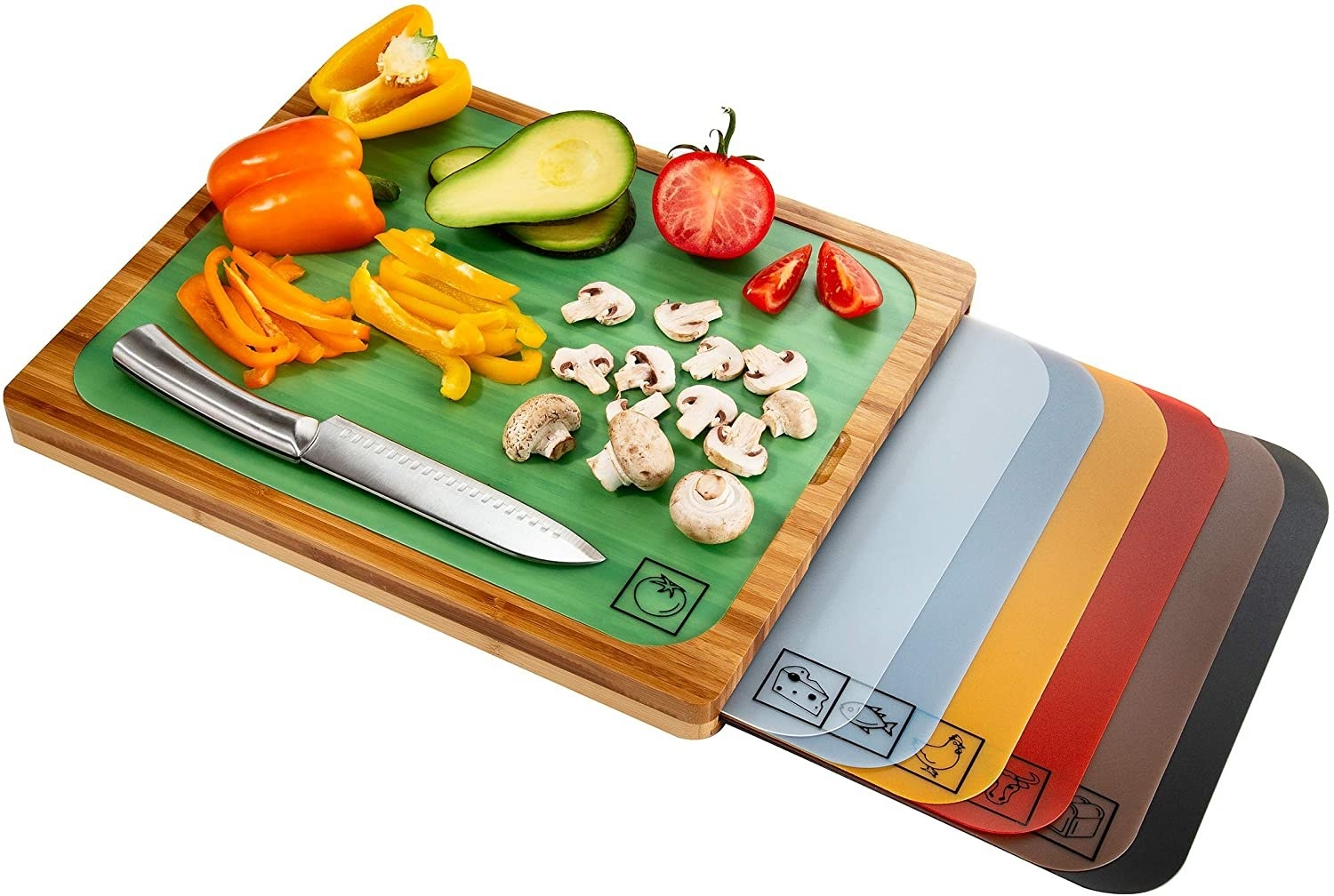 A bamboo cutting board with a green mat inserted on the top with a knife and vegetables on it next to six different colored mats each with a different food icon in the bottom right corner