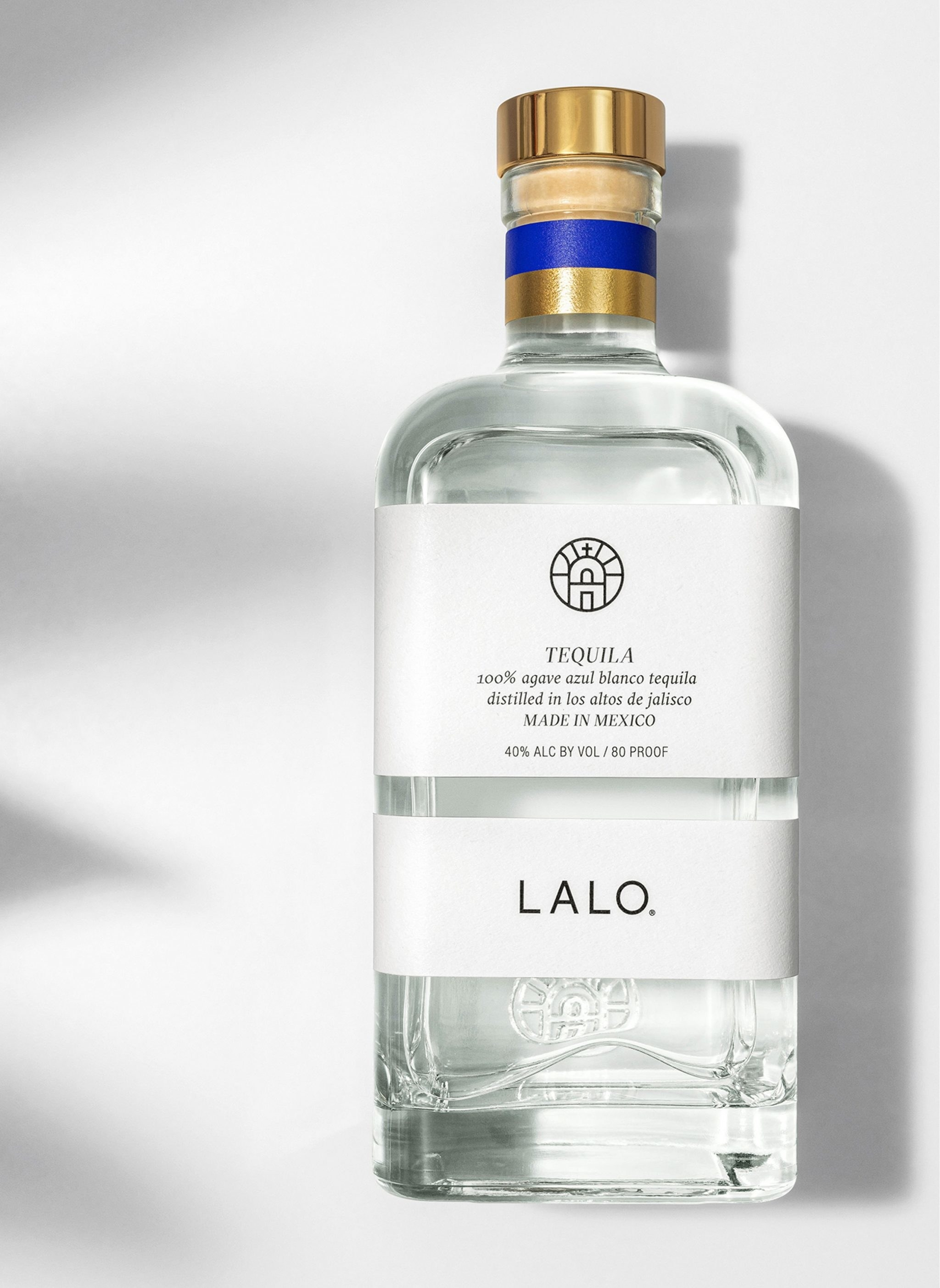 A bottle of tequila set on a white table top