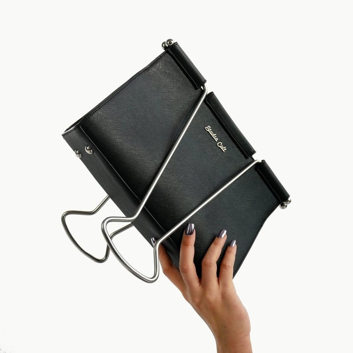 model's hand holding the bag which is shaped like the thick black paper clips that close and open with two silver handles