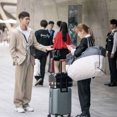 Ahn Jeong-ha and Sa Hye-jun standing together, Jeong-ha with her super huge makeup bag and suitcase