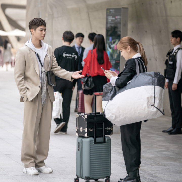 Ahn Jeong-ha and Sa Hye-jun standing together, Jeong-ha with her super huge makeup bag and suitcase