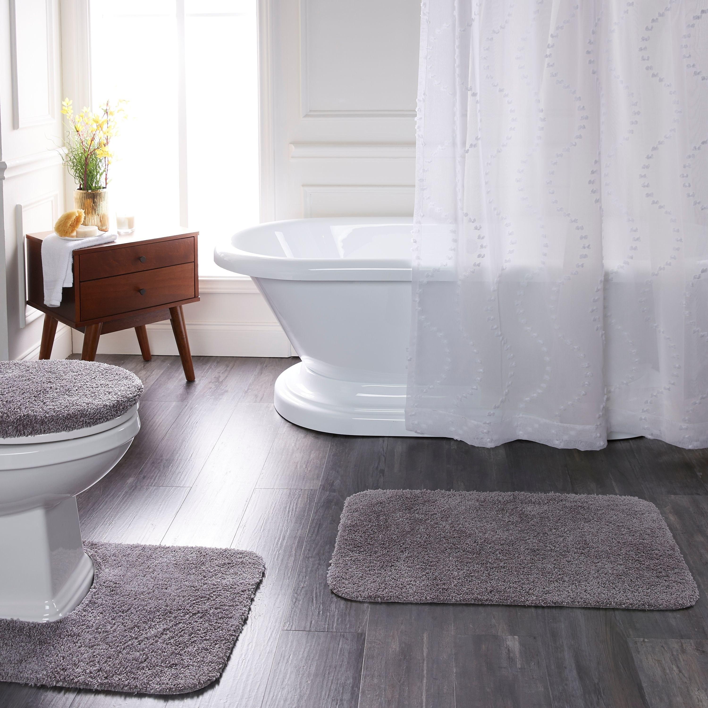 grey bath rugs on a bathroom floor