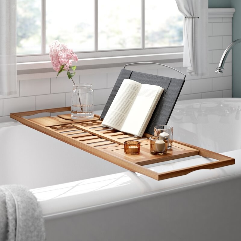 Bamboo bathtub caddy with book, vase and candles placed on top