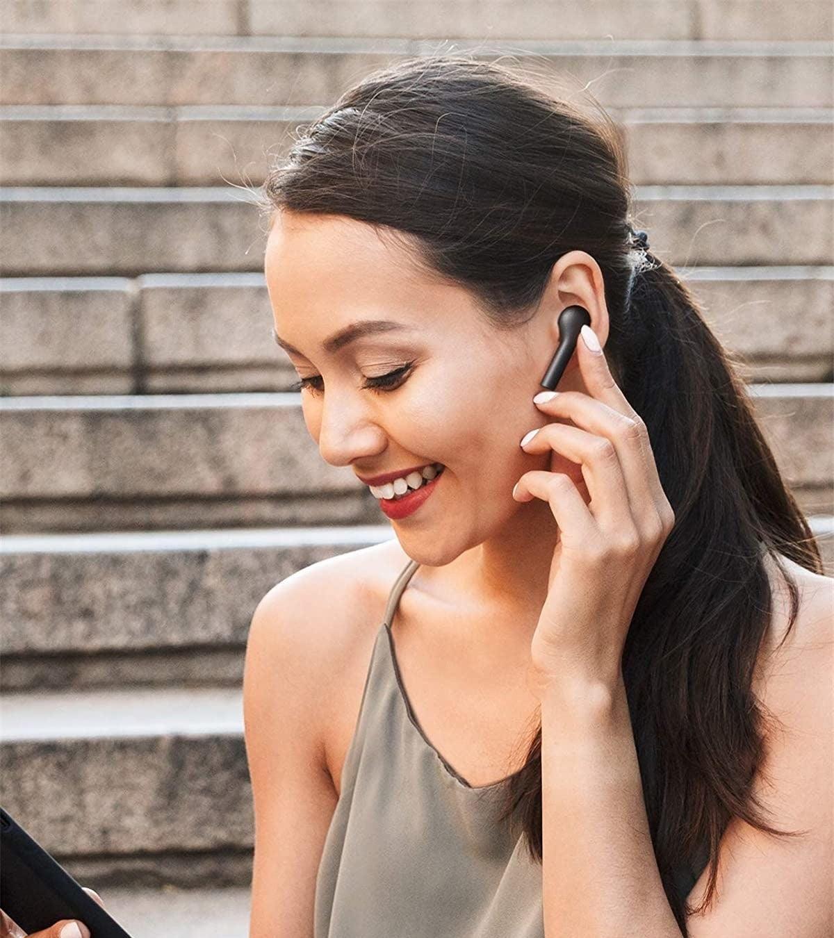 Model touching wireless earbud in left ear