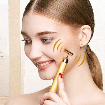 Model using T-shaped vibrating facial massager