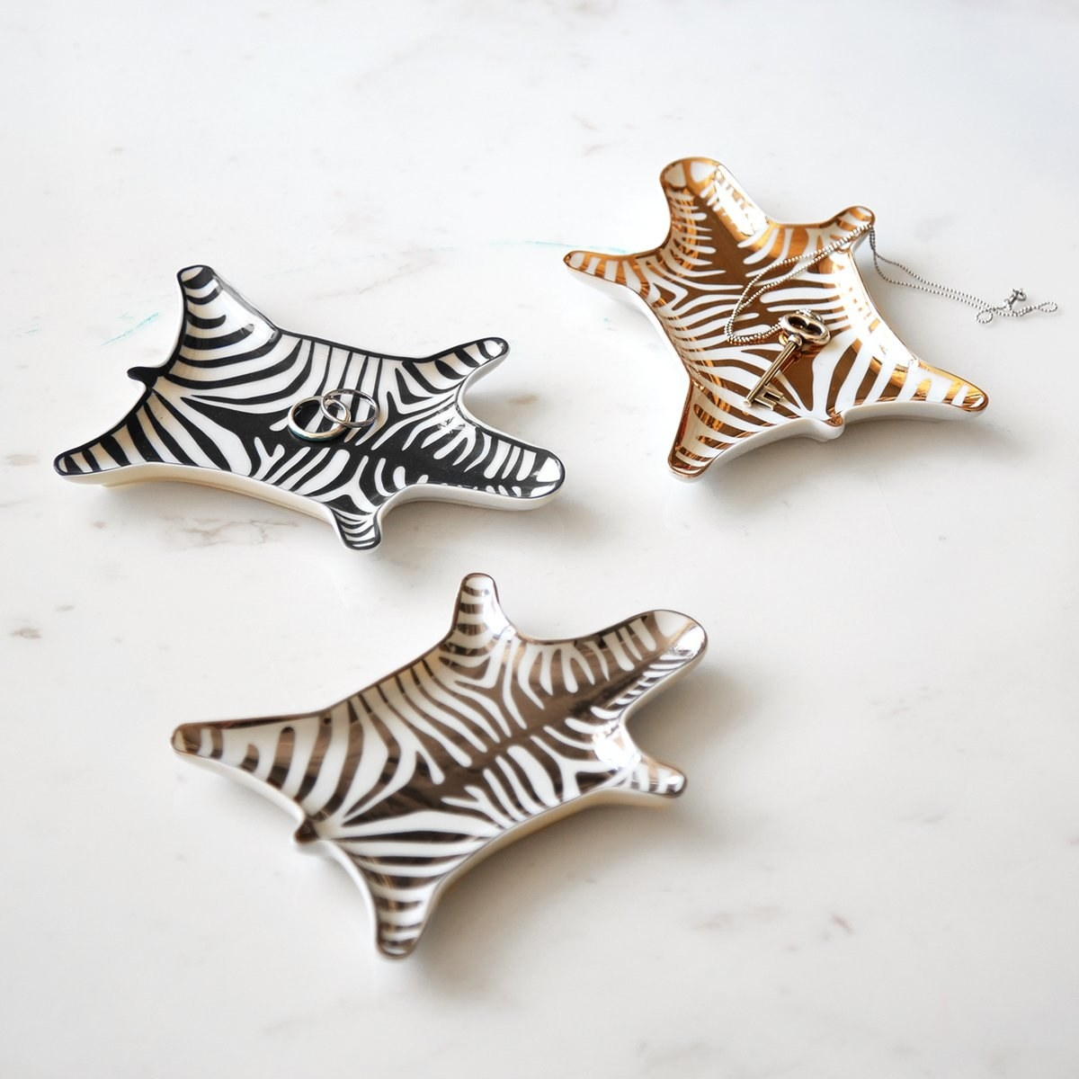 Three zebra-shaped trinket dishes in various colors