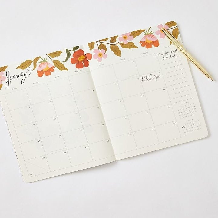 Planner opened to reveal monthly view with floral print on the top