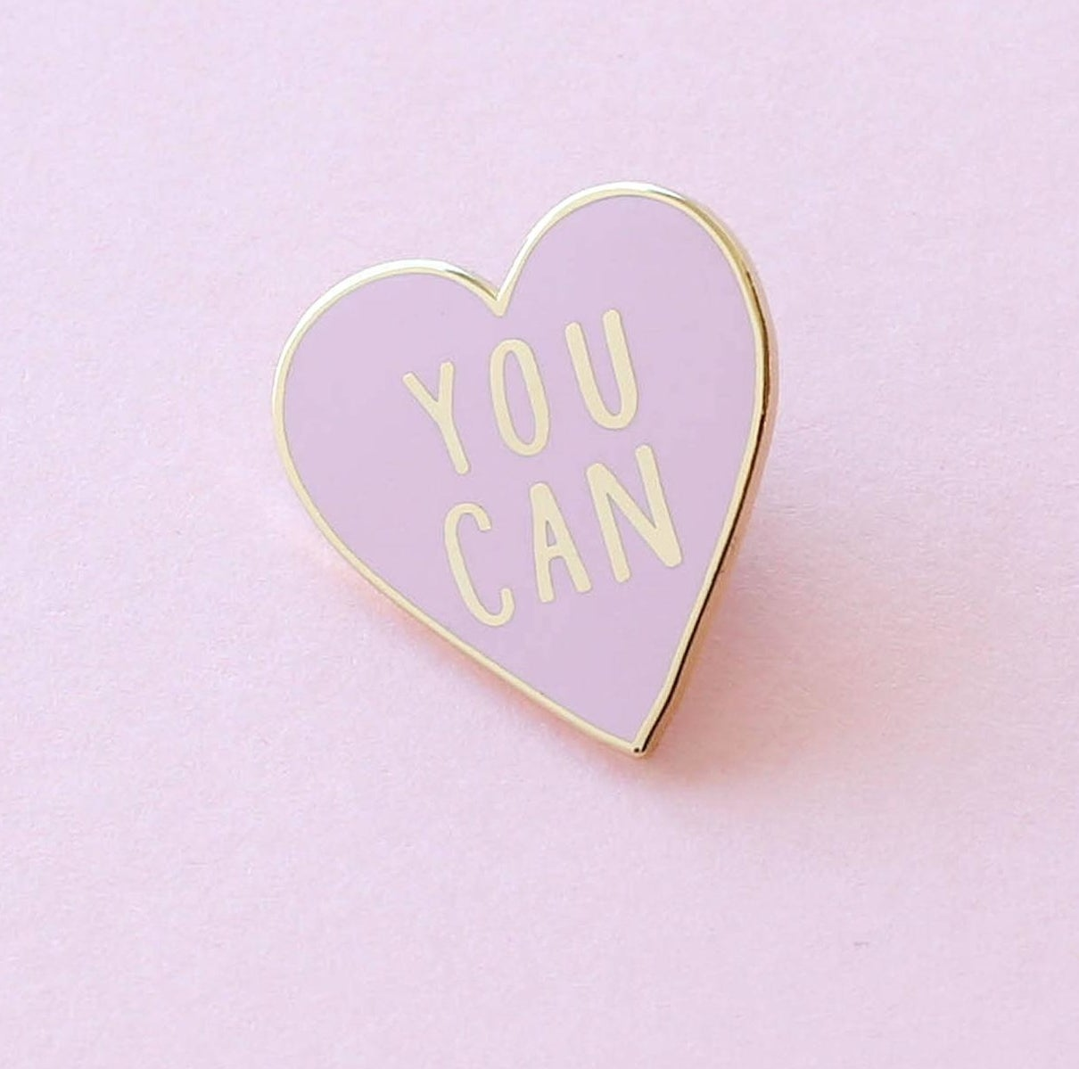 """A pink, heart-shaped enamel pin that says, """"You can"""""""