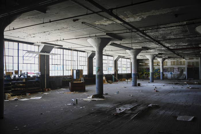 Photograph of the interior of an abandoned textile mill, featuring a wide open room with pillars, wooden floors and remaining debris. The large span of window panes radiate light onto the immensely large wooden floor.