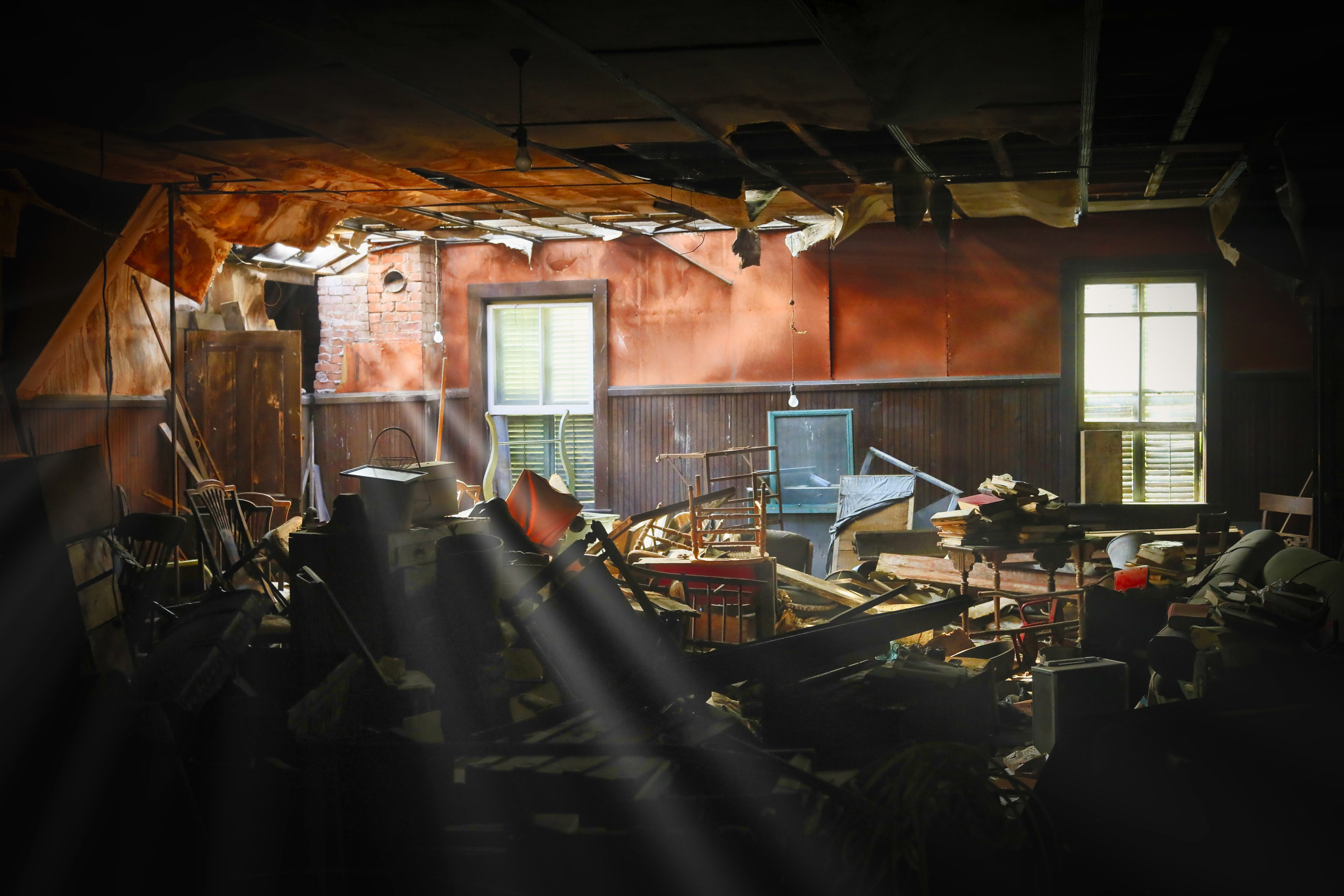 Beautiful, bright light radiating and streaming through a hole in the roof into a room filed with vintage furniture and historical relics.