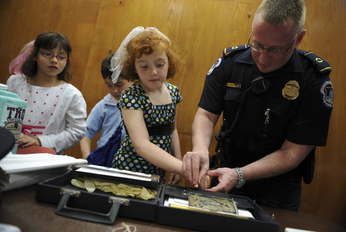 A police officer presses a young girl's fingerprints into an ink pad