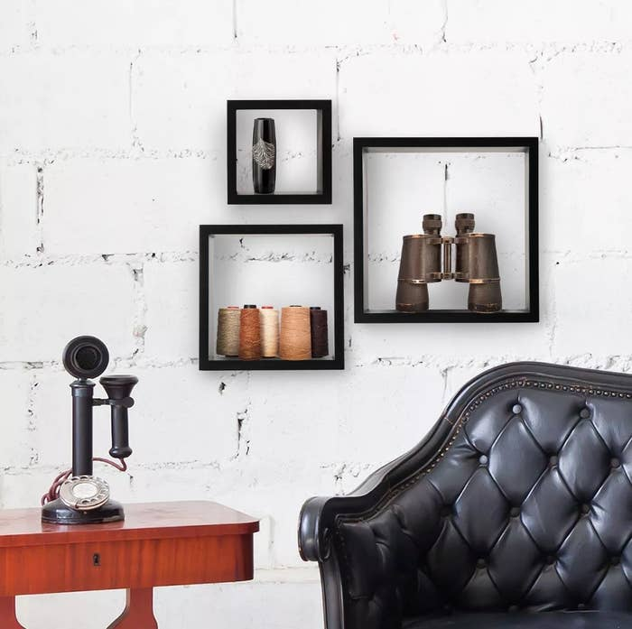 Three black cube wall shelves on white wall