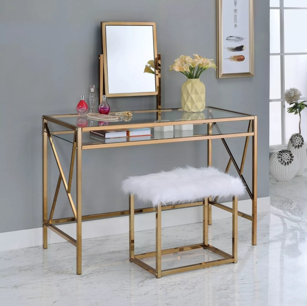 A vanity with mirror, gold frame, glass top, and matching white faux fur seat