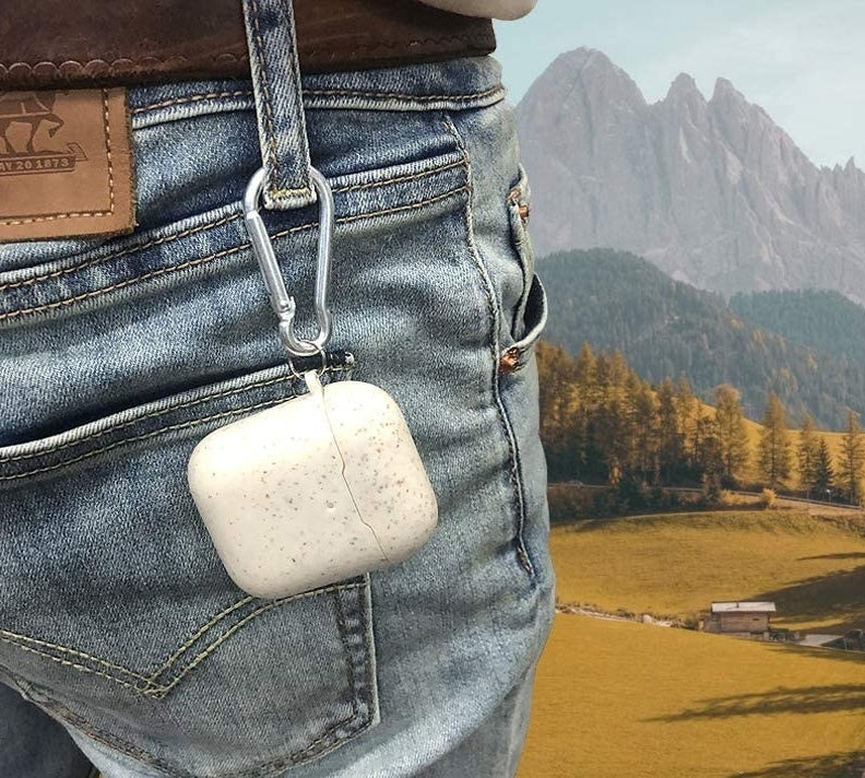 A person with their AirPods case on a carabiner attached to the belt loop on their jeans