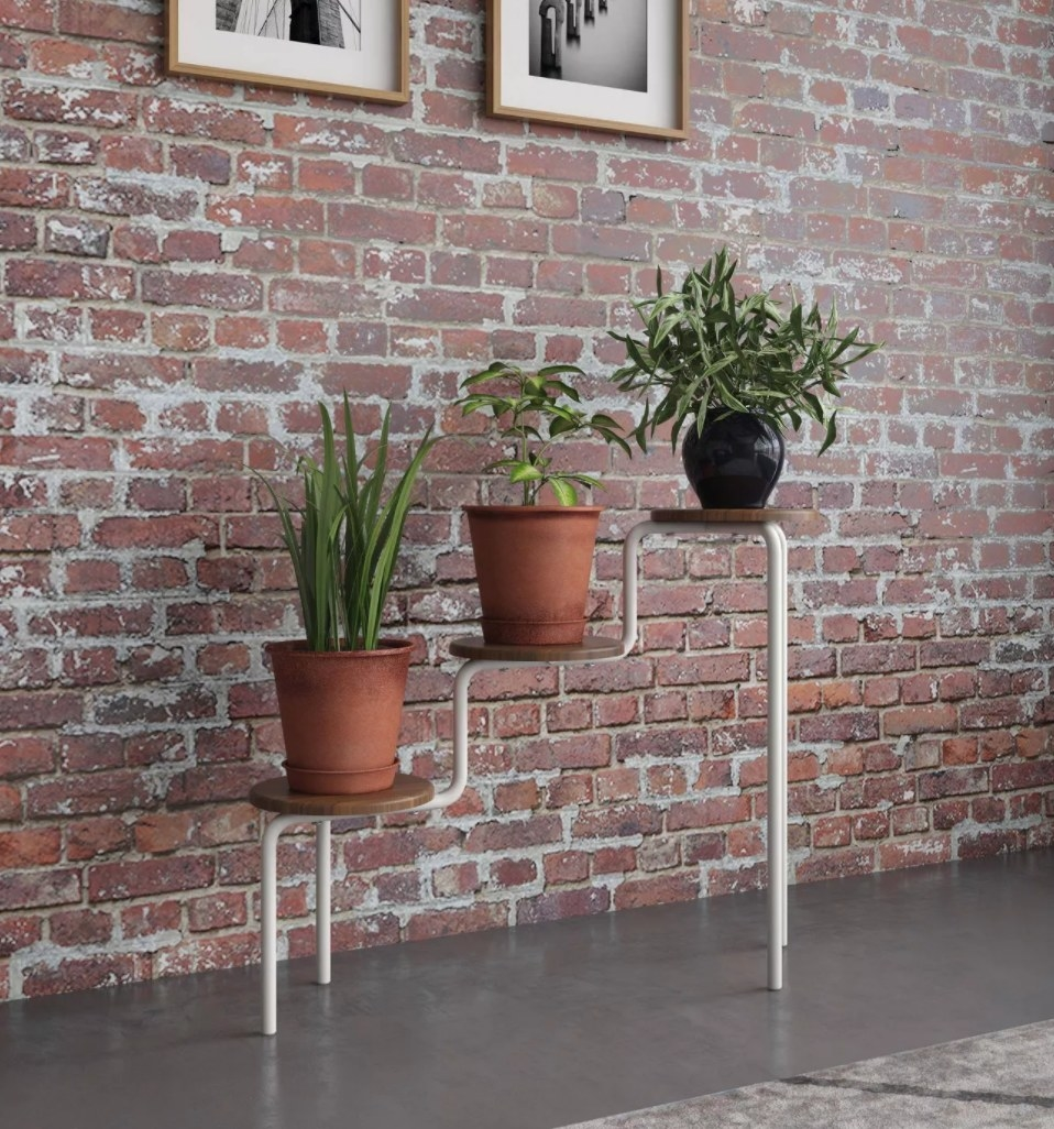 A three tiered plant stand with round wooden shelves and metal legs