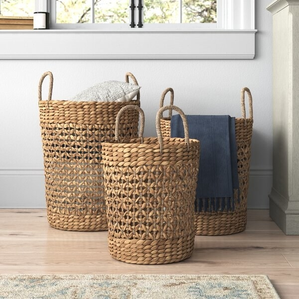 The three baskets, which are made of light brown wicker and which have handles and are each of slightly different heights