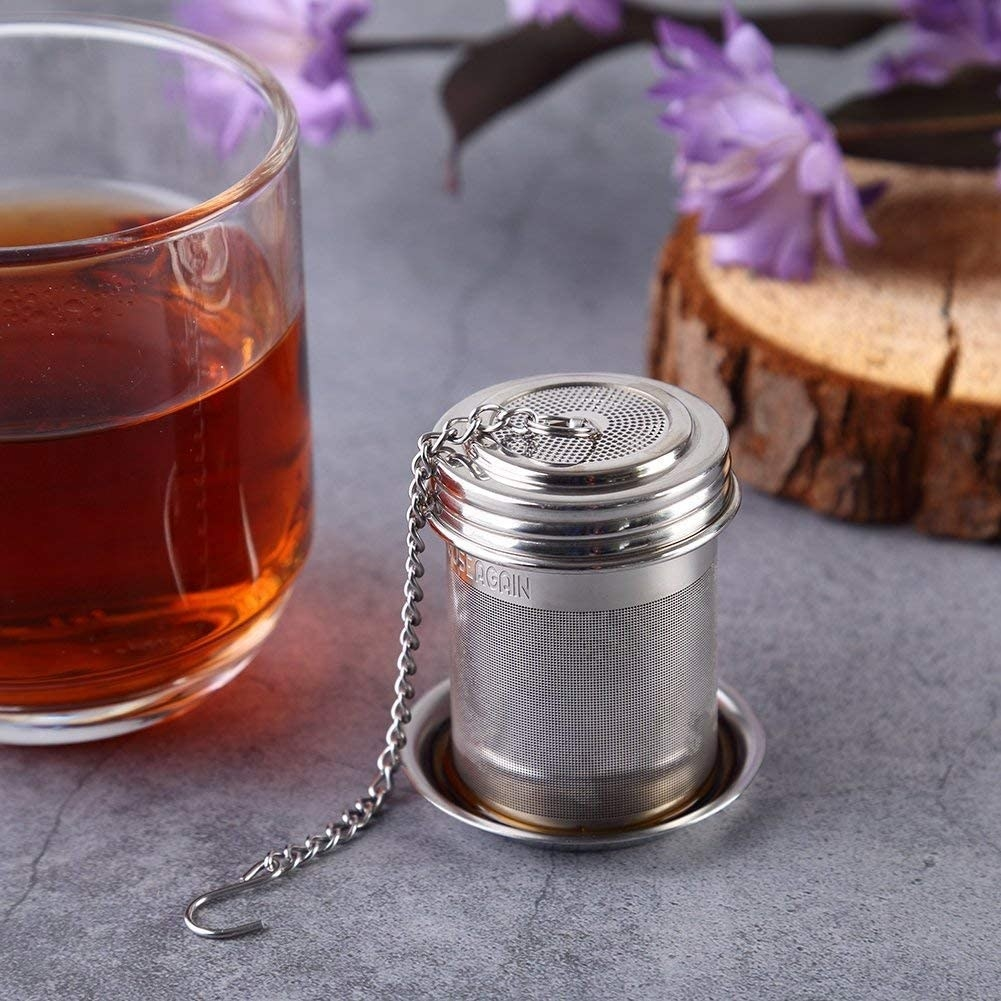 The infuser on a thin metal plate next to a glass of tea