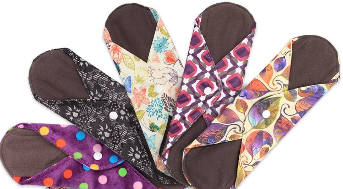 Bright patterned reusable menstrual pads with button clasps on their wings