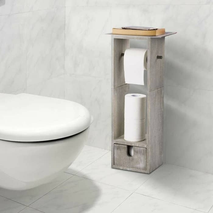 The toilet paper holder, which is long and rectangular, with a flat shelf on top, a rod for hanging the paper, a storage area to stack unused paper, and a small storage drawer at the bottom